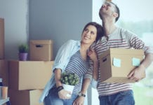 Happy young couple unpacking boxes and moving into a new home.