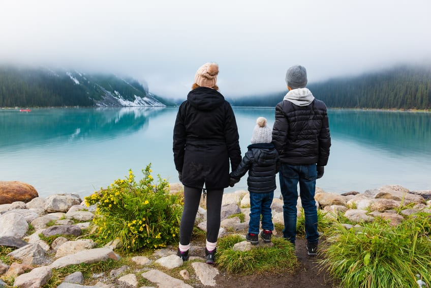 Young family admiring the view at Lake Louise (Canada) on a foggy day