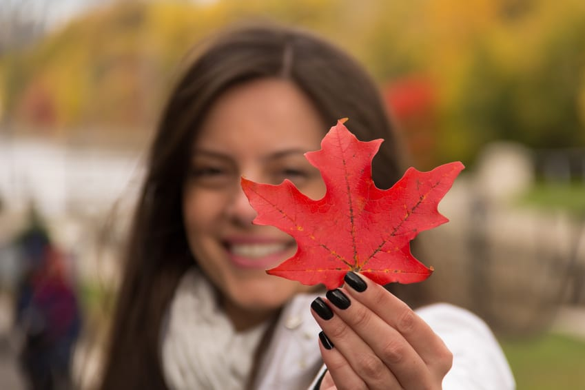 Smiling girl holding red maple leaf (Canada´s symbol)