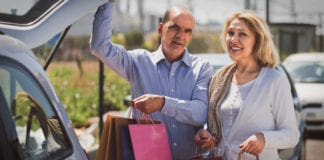 Smiling elderly couple putting bags with purchases in trunk