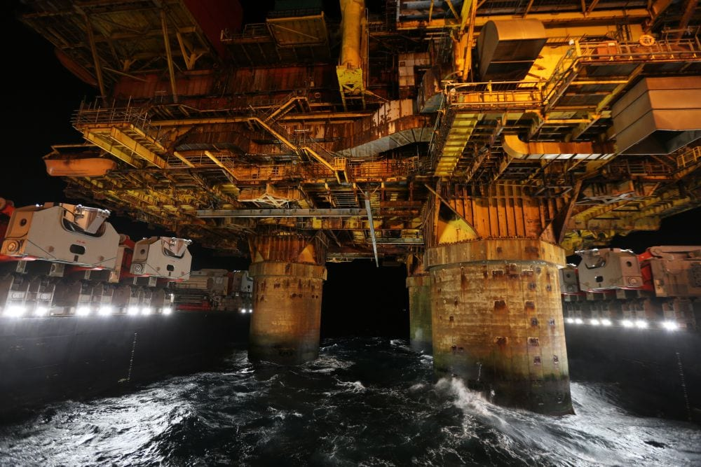 The topside of the Brent Delta rig is painstakingly loaded on to the ship.