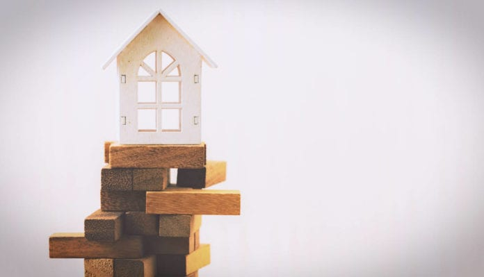 Model house balancing on wooden blocks