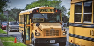 American Yellow School Bus parked at sidewalk